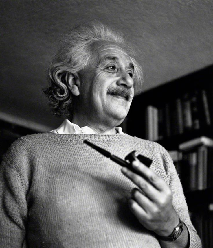 A smiling Albert Einstein at home in his Princeton study, with a favorite pipe and tobacco tamper in one hand.