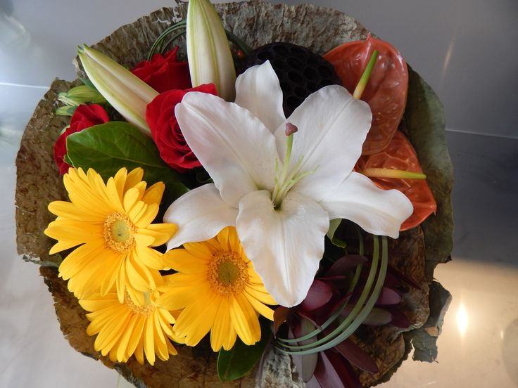 Euorpean style bouquet with groupings of different flowers wrapped in lotus leaves. Order it now from our website to be delivered to any Gold Coast suburb.