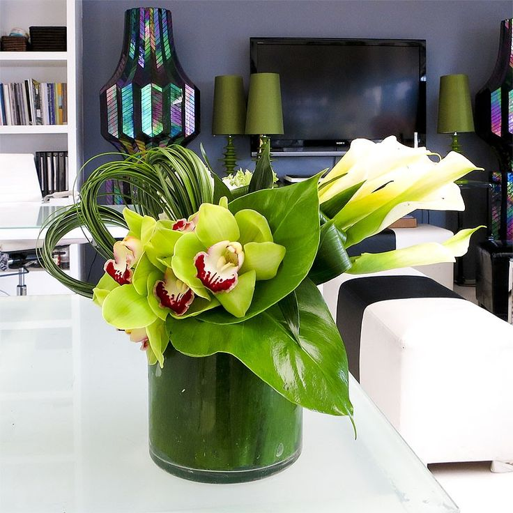 A smaller arrangement with Green Cymbidiums, White Callas and greens in a very minimalist modern arrangement. vase: 6 in diameter $75.00