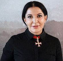 """Marina Abramović--(born 1946) is a Serbian performance artist based in Ny. Her work explores the relationship between performer and audience, the limits of the body, and the possibilities of the mind. Active for over three decades, Abramović has been described as the """"grandmother of performance art."""" She pioneered a new notion of identity by bringing in the participation of observers,"""