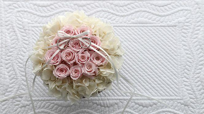 12本の清楚な淡いピンクのバラと白いあじさいをあふれるように生けたリングピロー。その12本のバラ(dozen roses)にはそれぞれ意味があり、「感謝・誠実・幸福・信頼・希望・愛情・情熱・真実・尊敬・栄光・ 努力・永遠」を象徴
