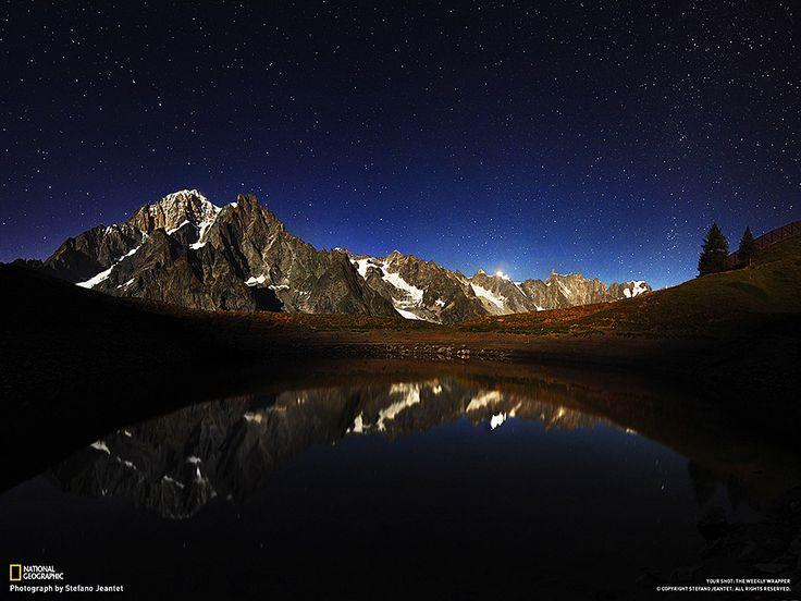 Fotografia di Stefano Jeantet  La foto ritrae la catena del Monte Bianco riflessa nel lago Checrouit, a Courmayeur, in Italia. Ho scattato nove fotografie e poi le ho unite, regolando le curve e ricomponendo il panorama. Era una notte di Luna, ecco perché la montagna è illuminata.