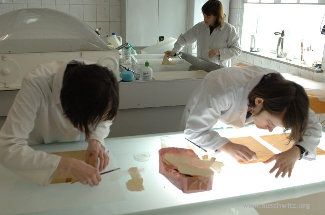 Preservation of archival documents of the SS-Hygiene archival collection at the Auschwitz Memorial conservation lab.     Furnished with all essential research and conservation equipment, the conservation studio is among the most up-to-date in the world.