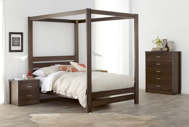 Springwood dark four poster wood grain bedroom furniture suite with natural beige and pastel orange linen and décor