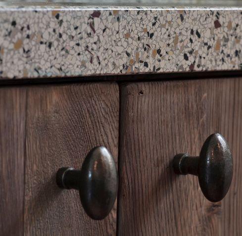 Alle elementen samen maken het plaatje compleet, stoere robuuste deuren van verouderd eiken, terazzo blad en elegante knoppen.