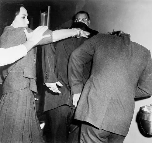 Marlon Brando during his courtroom battle to win increased visitation rights to son Christian; his ex-wife, Anna Kashfi, is on the left delivering a smack, 1961.