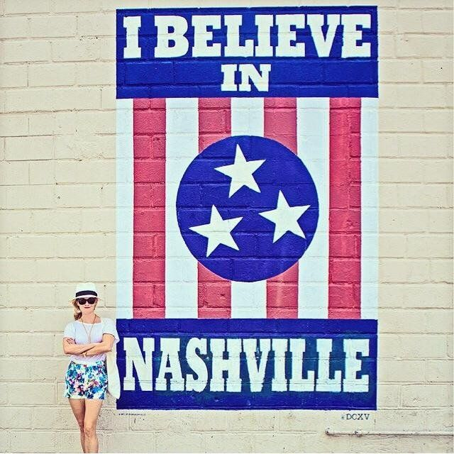 Reese Witherspoon standing in front of the I Believe In Nashville mural located…