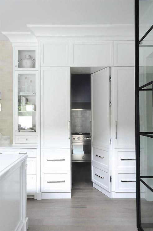 a kitchen pantry is hidden behind white woodpaneled doors