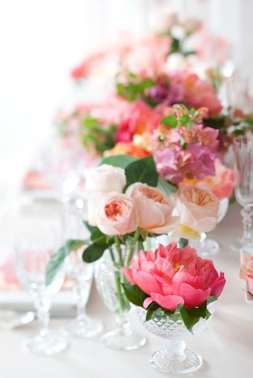 blossoms in crystal glasses. floral tablescape.