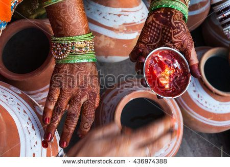 Traditional Indian wedding ceremony. In the pots applied symbols, symbolizing happiness and prosperity. Woman's hands painted with henna - stock photo