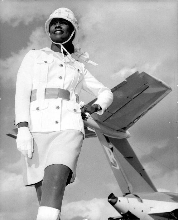 """A female bobby (policeman)? No! Just the new look of the stewardesses at Bahamas Airway. Designed by Mr. Bob Bride of New York, the outfit includes a white flowing cape and is part of the total expansion programme currently underway at BAL."""