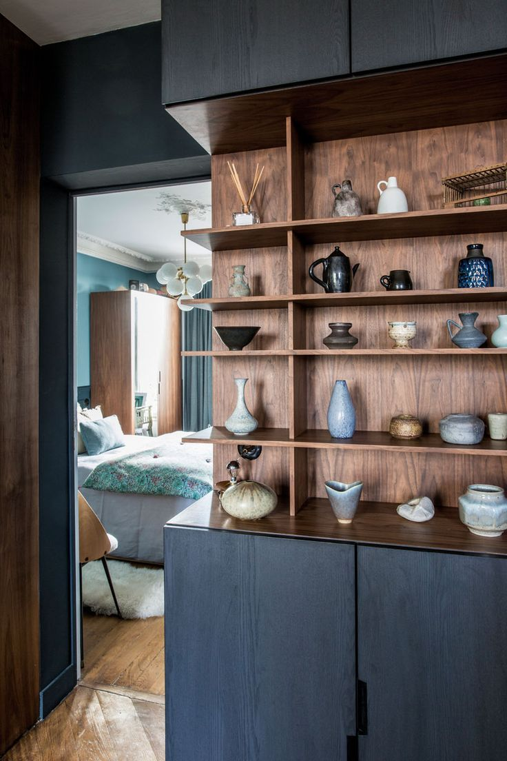 Styled wood shelves with vases, urns, and dishes, black cabinetry and a peek into the bedroom