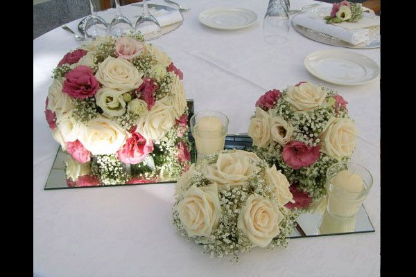 Un'altra proposta di centro tavola: grandi sfere di nebbiolina  e rose adagiate su piattaforme specchiate che riflettono la luce generata da...