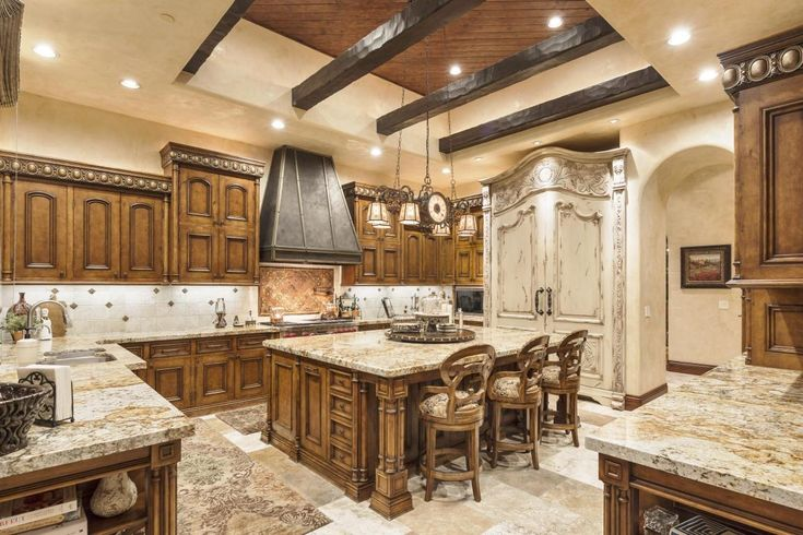 Mediterranean Style Kitchen with recessed lighting and exposed wooden beams that compliment the pendant lighting above the massive kitchen island.