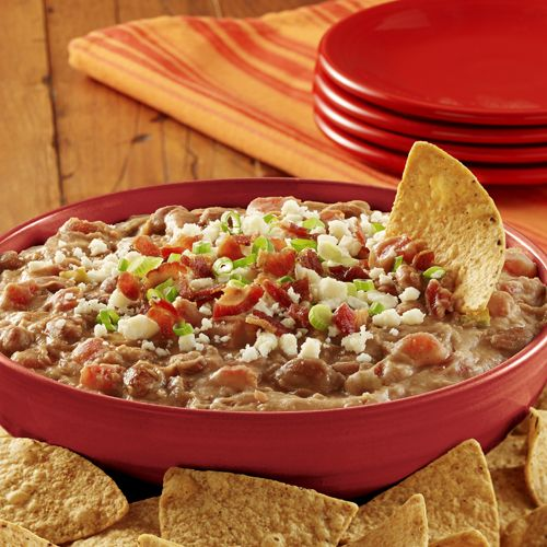 A warm bean dip recipe made with refried beans, zesty tomatoes and cream cheese, topped with crumbled bacon and queso fresco cheese