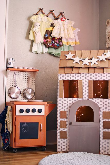 Cardboard box playhous for kids decorated with wallpaper and wrapping paper plus a star garland. The cardboard shingles are so cute! Fun DIY project for a rainy day.