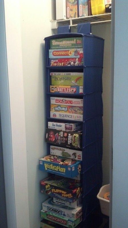 Store and organize board games with a repurposed hanging sweater rack! Great idea they take up so much space!