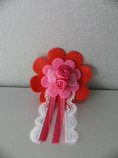 Broche Bloem Rood/Roze    De broche heeft een rode bloem van vilt op de achtergrond en een roze bloem van vilt op de voorgrond. De broche is verder gedecoreerd met 2 roze stoffen roosjes en een roze strikje.   De kanten, hardroze en lichtroze linten maken - € 4,00