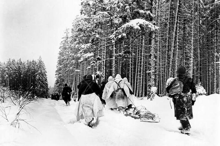 Des troupes de la 82ème Division aéroportée américaine, près de Herresbach, en Belgique, le 28 janvier 1945. À noté le lourd traîneau de munitions.