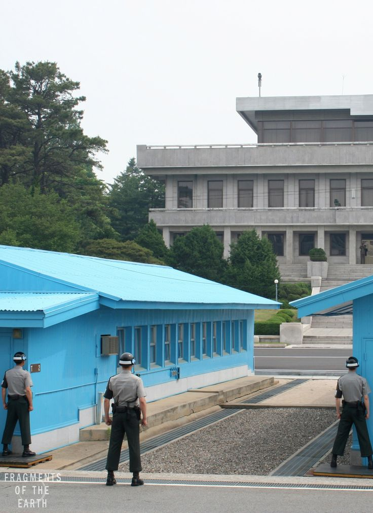 The blue huts of the Korean De-Militarized Zone (DMZ), seen from the South Korean side. The building in the background is part of North Korea.  The concrete line running through the huts is the official border between the two countries. The South Korean solders stand with half of their body obscured in order to provide a smaller target to those on the North, as well as to be able to signal unseen if necessary. www.fragmentsoftheearth.com