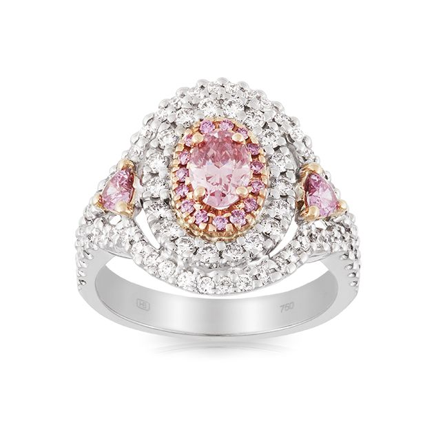The vibrant Pink Diamond centre gem comes to life in this striking 18 carat white gold ring from our Hardy Brothers Vault Collection. Complimented by a matching pair of heart cut Pink Diamonds on either side and a double halo of white Diamonds that sweeps down on to the shoulders this piece is truly spectacular.