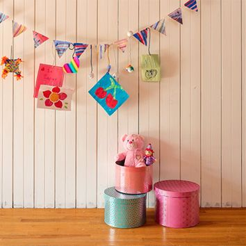 Turn an ordinary hallway into an art gallery by adding handcrafted garlands and colorful flags, and curating toys and boxes into a whimsical setting.