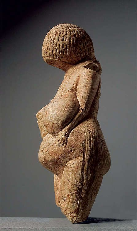 This figurine represents the Palaeolithic 'Venus', with overlarge breasts and belly. The faceless head bends towards the chest while the arms are pressed to the body with hands on the belly. Covering the surface of the head are rows of incisions indicating a hair style or cap. Relief work in the form of a tight plait convey a breast ornament tied up at the back. There are bracelets on the arms.