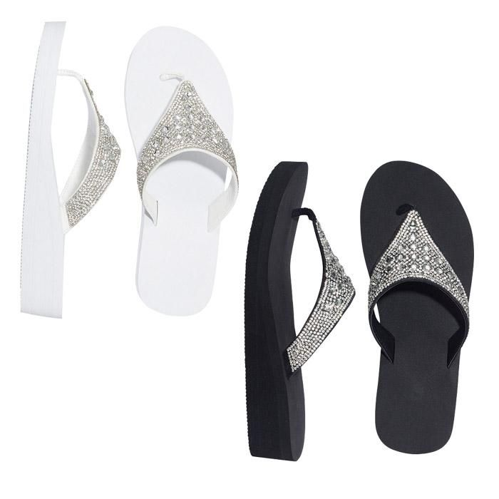 """Dress up or dress down with flip-flops that match any occasion. Whether you're hitting the beach or dining out, these shoes are always a go-to. Comes in black or white.  MATERIALS• PU (Polyurethane)• TPR (Thermal Plastic Rubber)    FEATURES• Clear diamonds on upper part of thong• 1 ½"""" wedge• Half sizes, order one size down  CARE• Wipe with a dry cloth."""