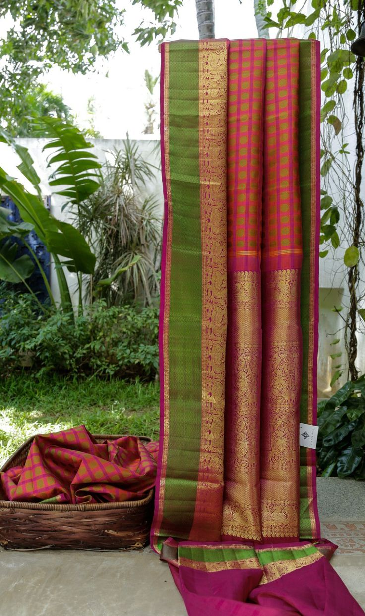 This traditional sari is in strawberry pink chequered with magenta thread work with round bhuttas in emerald green. The border is in magenta and emerald green with gold zari work and the palluis i…