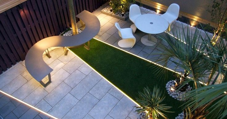 Modern Garden Design With Curved Shape Table And Round White Table Outdoor Living Room Plus Grass Mix Paving Flooring And Line Lighting.