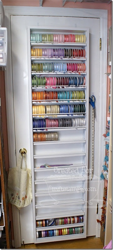 Ribbon storage built on the back of a door. Allows you to see what you have at a glance and keep organized. Small dowels help to hold spools in place and feed ribbon through on the bottom. Scissors and measuring stick/tape kept with it. - from paper pursuits