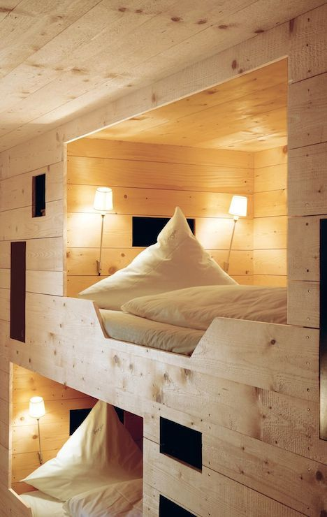 Rustic wood paneled bunk room with built-in bunks featuring cut out steps and beds with individual sconce lighting.