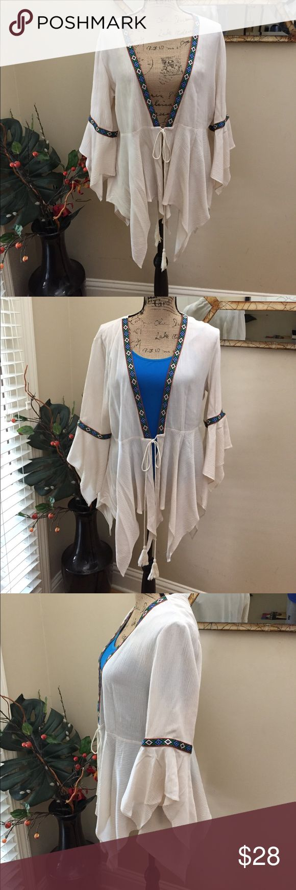 """Entro handkerchief hems BOHO kimono/blouse! Entro handkerchief hems BOHO kimono/blouse! This is a super fun hippie chic top with bell sleeves and multiple hem lengths. It has s tasseled tie in front and will require a bra or cami underneath. (Pictured with a blue cami for example). I wore this once and have the most recent dry cleaning tag on the Entro tag. Aztec turquoise green rust detail. Stunning. Preloved in excellent condition. Pit to pit measurement (tied) is 19"""". Length is 26""""…"""
