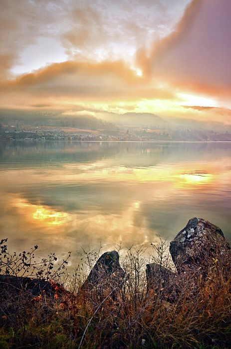 A new day begins with the clouds and light reflected in the still waters of Skaha Lake in Penticton, BC canada