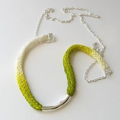 spool knitting all grown up... Brenda gives the white silk ribbon an ombré effect by coloring it with acid green chartreuse fabric dye. The curved metal tube is the perfect focal point.