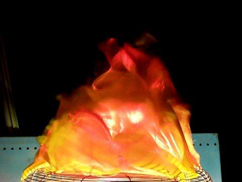 white plastic bag, spray painted fire colors..secured to old desk fan, set into…