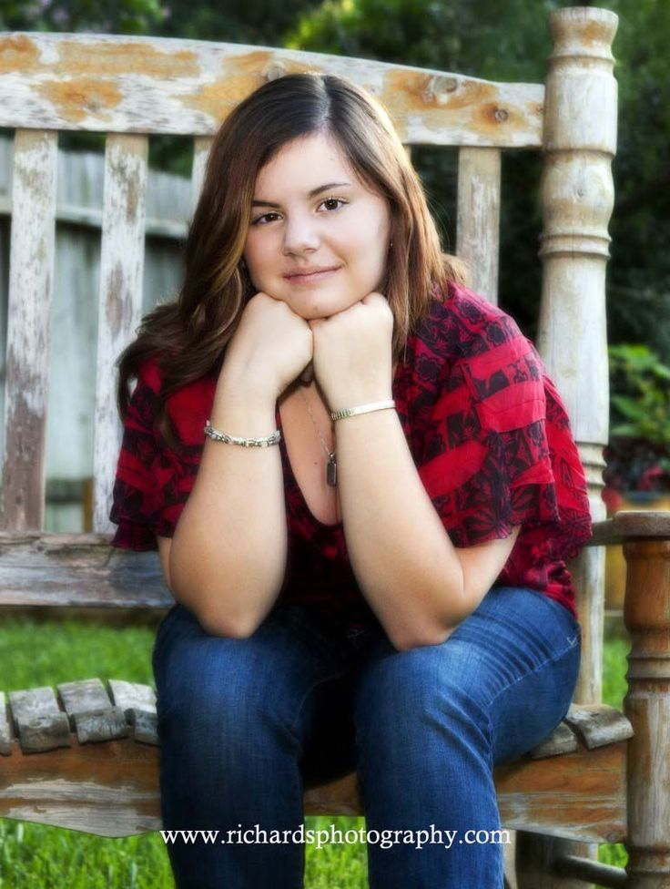 High school senior sitting on old fashioned rocking bench in the outdoor studio.