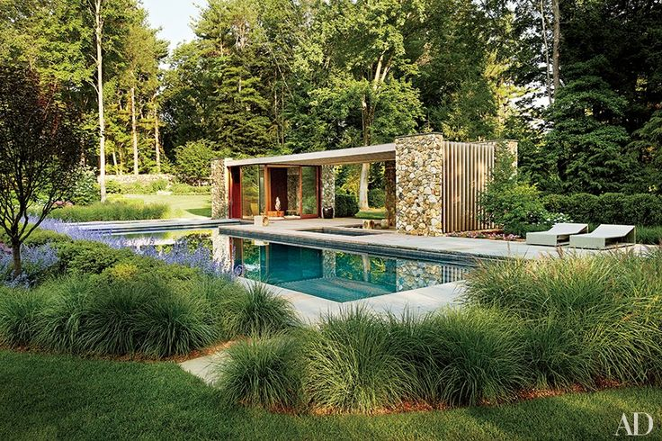 A poolhouse in Westport, Connecticut, designed by New York City architecture firm SPaN, is distinguished by fieldstone walls and a slatted cedar pergola. On the bluestone terrace, the chaise longues are by Janus et Cie; the landscape design is by Rutherford Assoc.