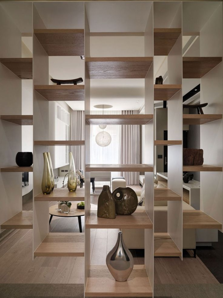 Display shelving is a room divider, giving showcase for ceramic art and sculpture