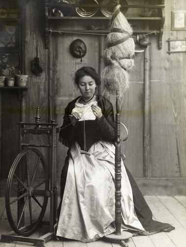 A girl sits at a spinning wheel and spins thread onto a spindle. Location: Switzerland.