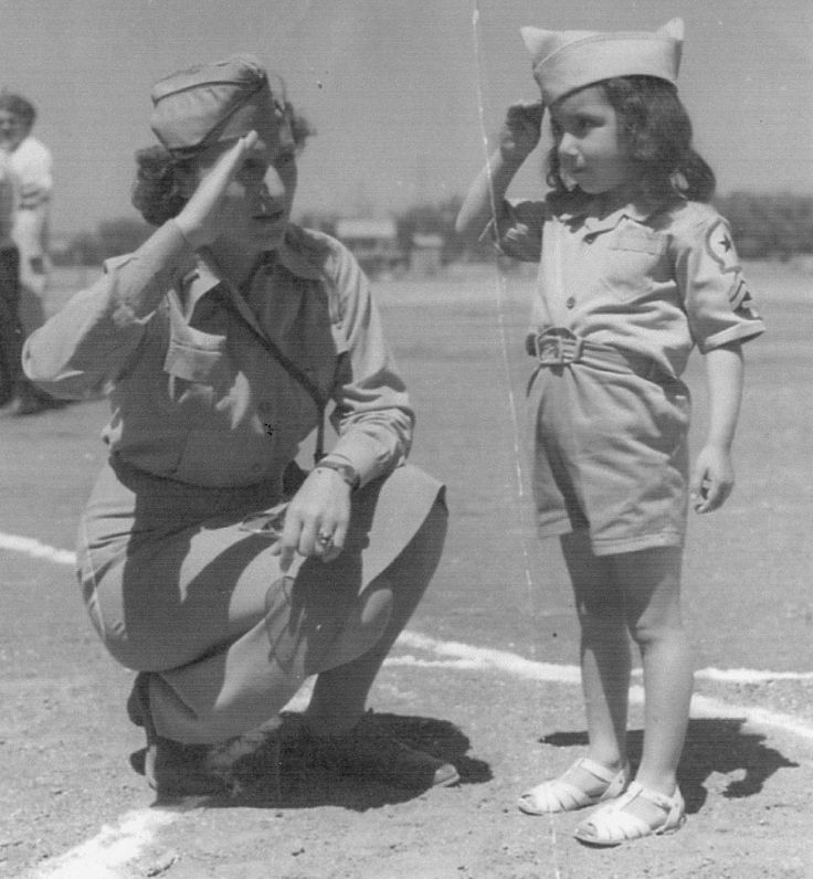 Lt. Elizabeth Ray returns the salute of an Italian girl she befriended at their base, 1944