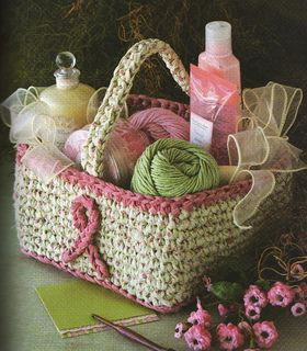 """From designer: """"This basket is crocheted with fabric strips. I used 2 1/4 yds off-white and 1 1/2 yds pink fabric cut into 1"""" wide strips. The basket measures 5"""" high x 8"""" square. There are 2 pink ribbons made from fabric strips that are glued onto 2 sides of the basket for Breast Cancer Awareness. There is an optional crocheted fabric handle added, also. This basket can be used for almost anything and made in any desired colors of fabric. This was my first project using fabric strips for…"""