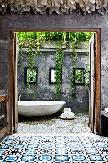 This could just be my ultimate bathroom. Look at the concrete walls, the wooden cabinets and door frame, and a stunning tiled floor. And the bath is outside!