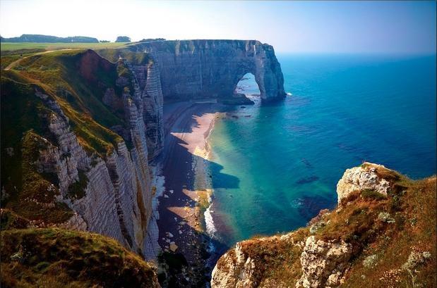 Etretat, França: situado na região da Normandia, no norte do litoral atlântico da França, o vilarejo de Etretat é conhecido por seus imponentes penhascos que se encontram com o oceano.  A 40 metros da praia da cidade, os penhascos brancos cobertos de vegetação têm o auge beleza em seus arcos brancos | Foto: Moyan Brenn