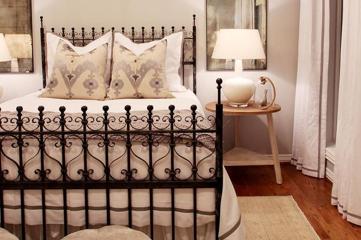 Chic bedroom features an iron scroll bed dressed in white and gray bedding as well as cream and purple ikat pillows flanked by round wood bedside tables and white lamps under antiqued mirrors.