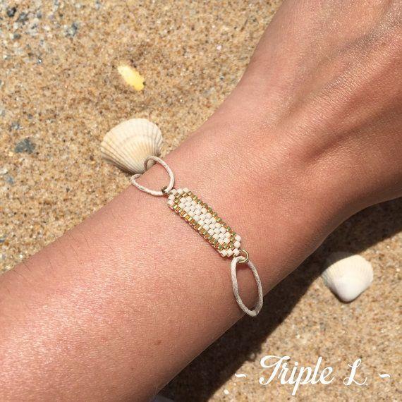 ~ DESCRIPTIF ~ Ce bracelet LAURENCE est composé dun tissage fait main avec des perles de verre Miyuki (tissées une à une à laiguille) et dun coton ciré fermé par des noeuds coulissants. Il est ajustable à toute taille de poignet (adulte ou enfant) grâce aux nœuds coulissants (faire coulisser les nœuds pour mettre le bracelet puis coulisser à nouveau les nœuds pour lajuster à la taille de son poignet). Couleurs des perles : blanc cassé - doré Dimensions du tissage : 0,7 cm x 2,6 cm…