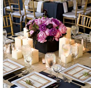 Purple centerpieces with square pillar candles.