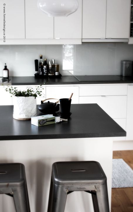 White cupboards with black benchtops.