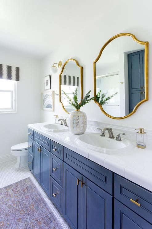two gold mirrors above a blue wooden dual washstand