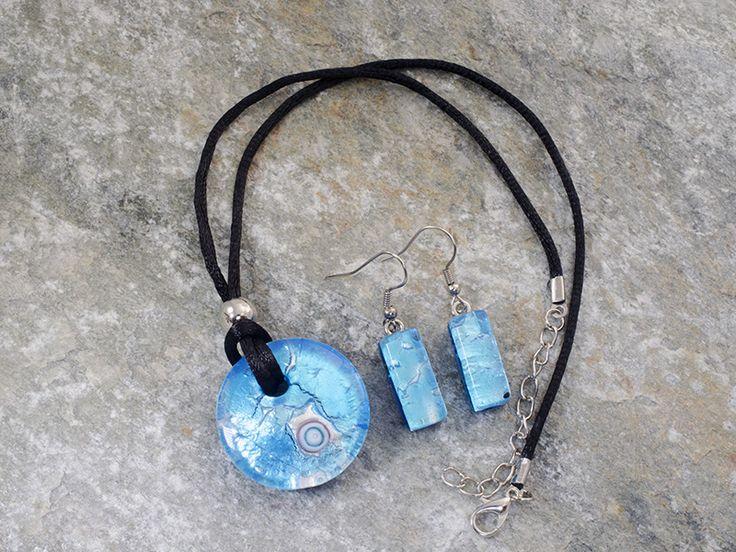 Parure un vetro di Murano con pendente rotondo, leggermente bombato, ed orecchini rettangolari.   Il laccio è in cotone nero.   Un pendente celeste con murrina centrale appoggiate su una foglia d'argento.